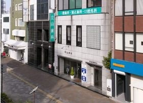 緑の看板が出ているビルです。一階で受付を行ってください。