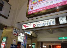 阪急 神戸三ノ宮駅を出てエスカレーターを降りますと当院の看板がございます。