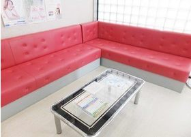 待合スペースです。赤色の大きなソファで、おくつろぎください。