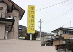 田口歯科医院の看板です。こちらの黄色い看板を目印でお越しください。