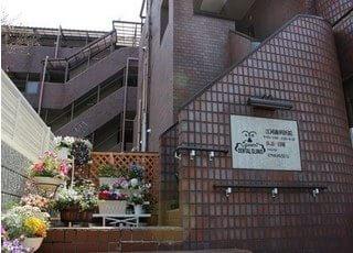 江河歯科医院の外観です。鉢植えには季節のお花が咲きます。