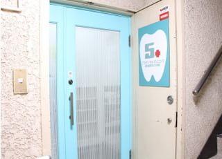 水色の枠のドアと歯の絵が描かれた看板が当院の入り口となっております。