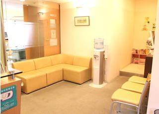 待合室です。暖かい雰囲気となるようオレンジを基調とした色で、お待ちの間でもリラックスできるようにしております。