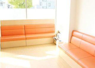 待合室にはあたたかみのあるオレンジ色のソファーがあります。
