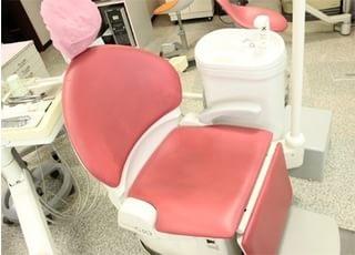 診療チェアはカラフルなピンク色です。