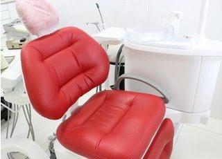 赤い診療チェアです。座り心地の良いチェアを使用しております。