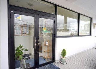 ひろし歯科クリニックの入口です。ドアにはロゴマークが飾られています。