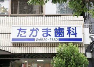 たかま歯科医院の外観写真です。こちらの看板を目印にお入り下さい。