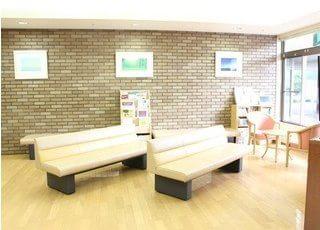 明るく開放感のある待合室です。ソファにお掛けになってお待ちください。