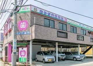 ピンクの看板がおかだ歯科医院の目印です。駐車場をご用意しています。