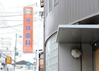 今井歯科医院の看板です。こちらのオレンジの看板を目印にご来院ください。