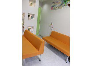 オレンジのおおきなソファでお待ちください。