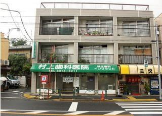 当院の外観です。緑の看板と雨どいを目印にお越しください。新高円寺駅から徒歩9分ほどにございます。