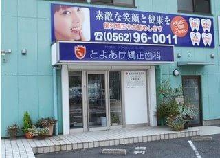 とよあけ矯正歯科の入口です。青色の大きな看板が目印です。