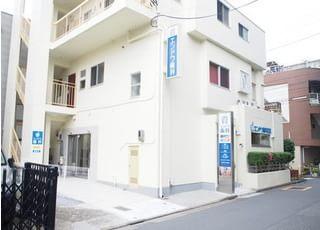 エンドウ歯科医院の外観です。白い建物と青い看板が目印です。