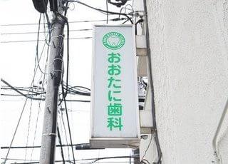 おおたに歯科の看板です。緑色のロゴを目印にご来院ください。