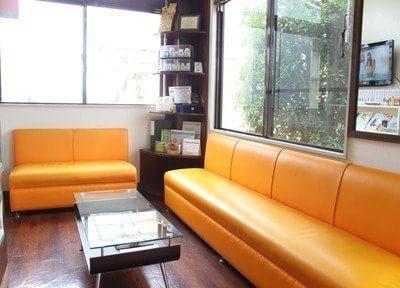 待合スペースです。オレンジ色の大きなソファで、おくつろぎくださいませ。