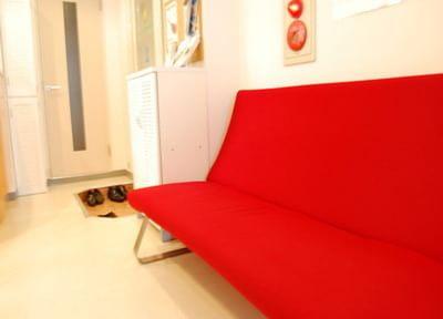 鮮やかな赤色のソファです。お掛けになってお待ちください。