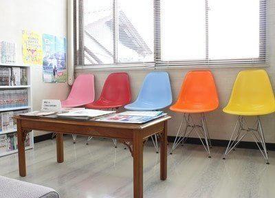 待合室の椅子はカラフルです。テーブルにはお口に関する小冊子等もあり、お持ち帰りいただけます。