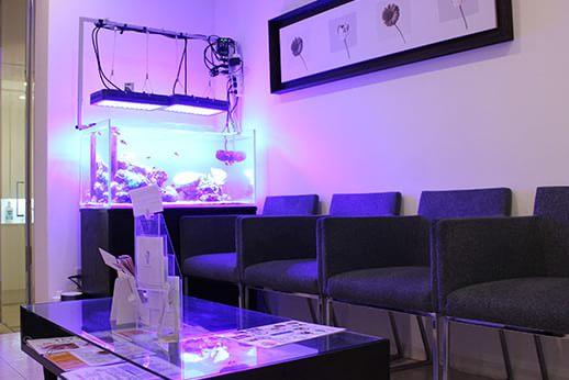 待合スペース。院長の趣味であるアクアリウムを設置し幻想的な雰囲気を演出しています。
