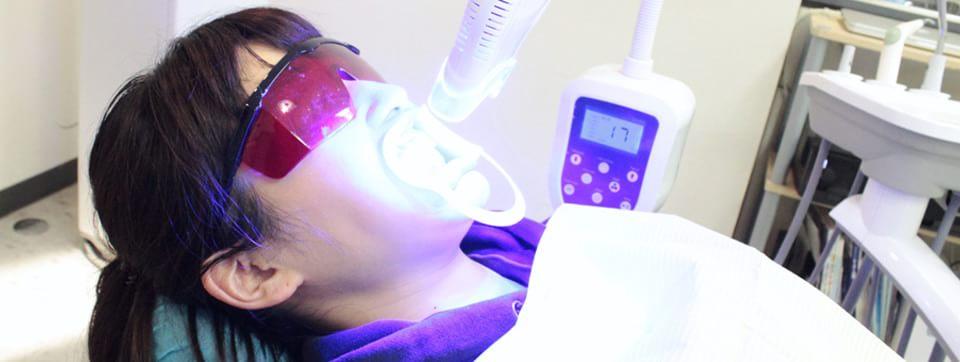 薬剤を塗った歯にライトを当てて施術