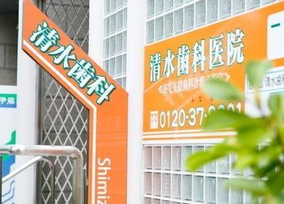 清水歯科医院の外観写真です。オレンジの看板が目印です。